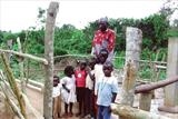 the Well Caretaker and Bugema village children by Deborah Elizabeth McNeill, Photography